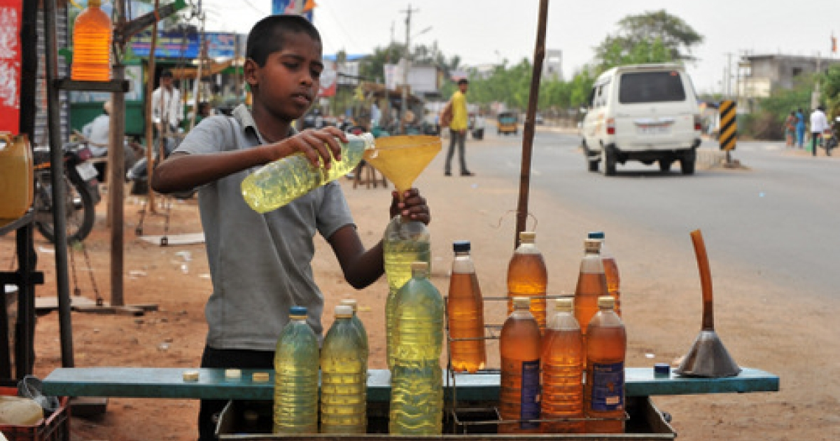 Indian boy Nagesh of the semi nomadic Lambadi tribe fills one liter bottles with petrol and diesel at a road side shop on the outskirts of Hyderabad on May 13, 2011. The prevalent use of diesel-powered generators -- thanks to India's chronic electricity shortage -- has become a serious environmental hazard.</p>