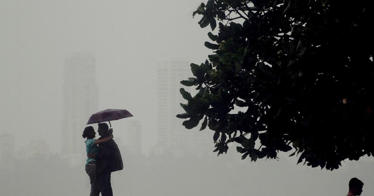 An Indian couple shelter under a umbrella as they enjoy heavy rain showers in Mumbai on September 3, 2012. The monsoon rains, a key to India's economy, covered the entire country on July 11 but it was 23 percent below average, officials said amid worries of its impact on two cereal-producing states.</p>