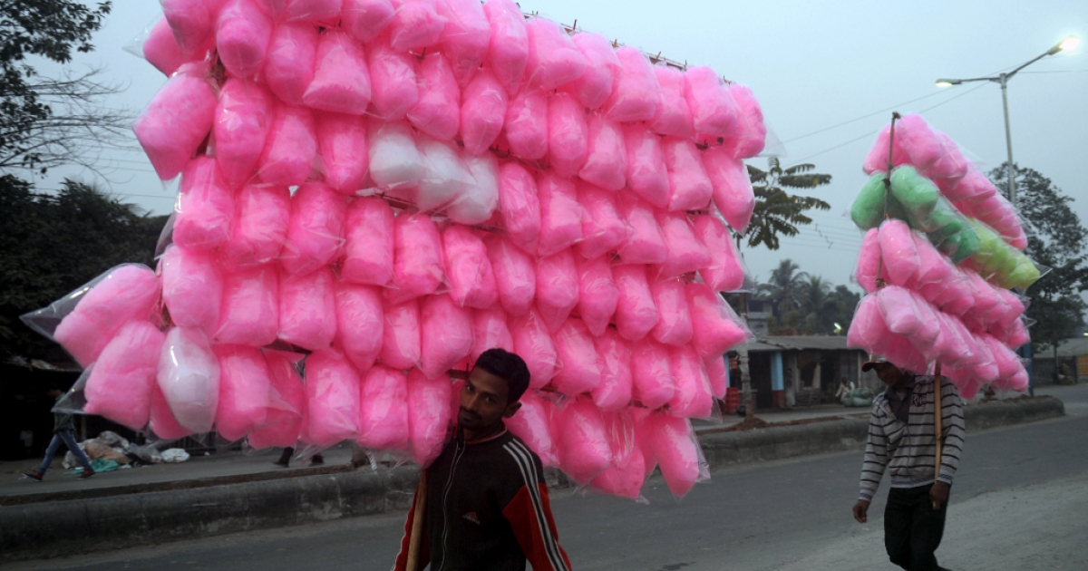Indian vendors carry cotton candy in Siliguri on November 25, 2012. India's economy logged around 5.5 percent growth in the last financial quarter, the finance minister estimated on November 24, 2012.</p>