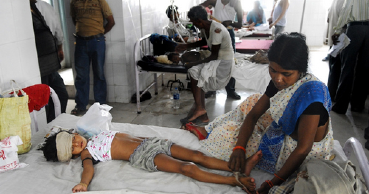 An Indian woman attends to a child lying in a bed of a hospital in Muzzafarapur, some 100kms north of Patna on June 23, 2011.  A deadly fever believed to be caused by a type of encephalitis has killed as many as 40 children in an impoverished region of eastern India, health experts said. The children died during the past week in the eastern Indian state of Bihar's Muzaffarpur district after experiencing high fevers followed by convulsions and unconsciousness, prompting the federal government to rush medical teams to the state.</p>
