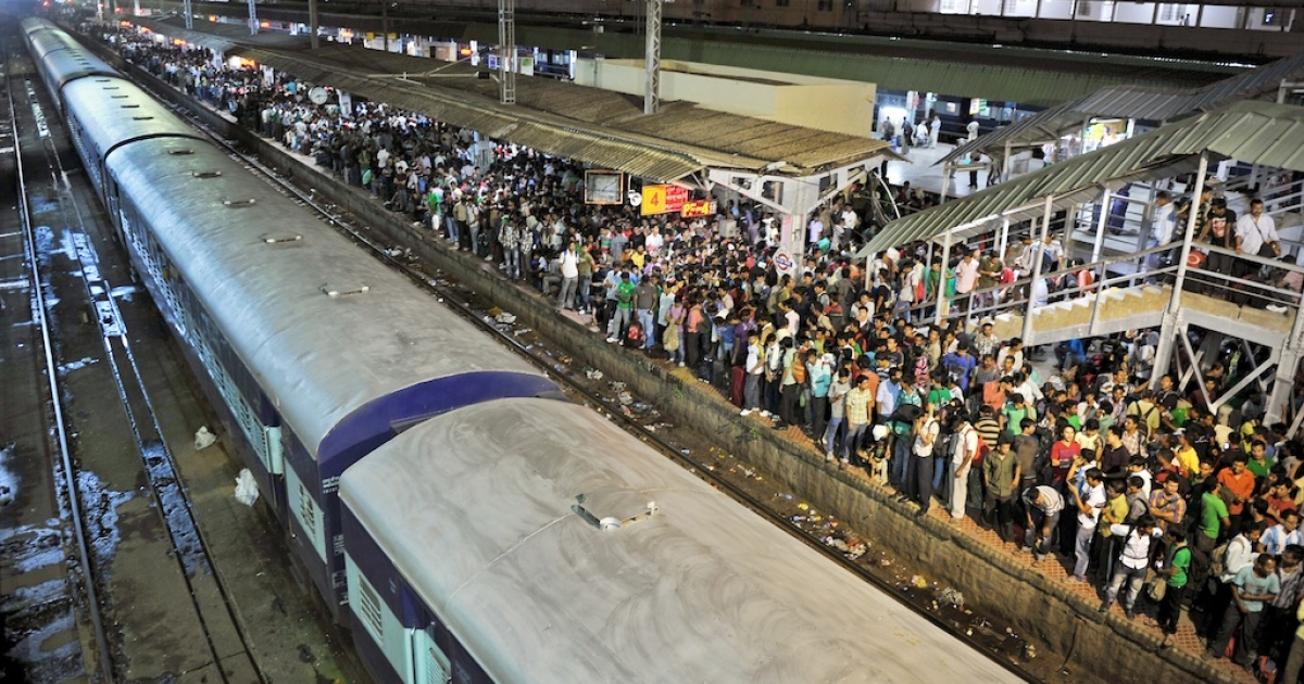 Indian minority residents wait on the platform of the city railway station to board trains.</p>