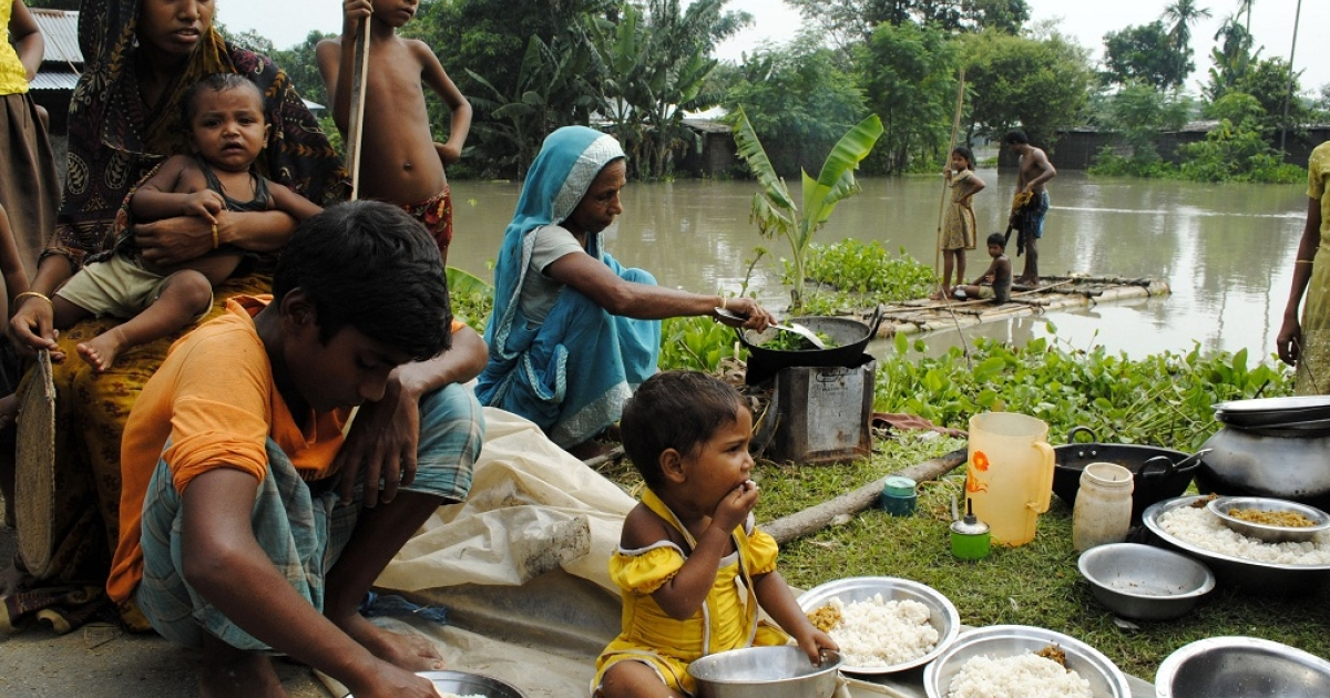 An Indian family eats alongside a road after their house was washed away by flood waters at Bulut Village, some 30 km away from Guwahati on June 30, 2012. Torrential monsoon rains triggered floods which swamped villages in eastern India and forced at least 2 million people to leave their homes for higher ground.</p>