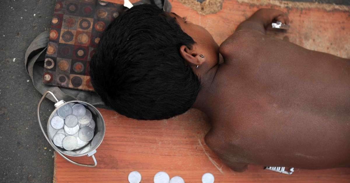 A handicapped child lies on a mat while begging for alms next to a few Indian rupee and paise coins given to him in Mumbai on December 7, 2011. Though it has plenty of problems at home, India initiated a global aid agency endowed with $15 billion for the next five years.</p>