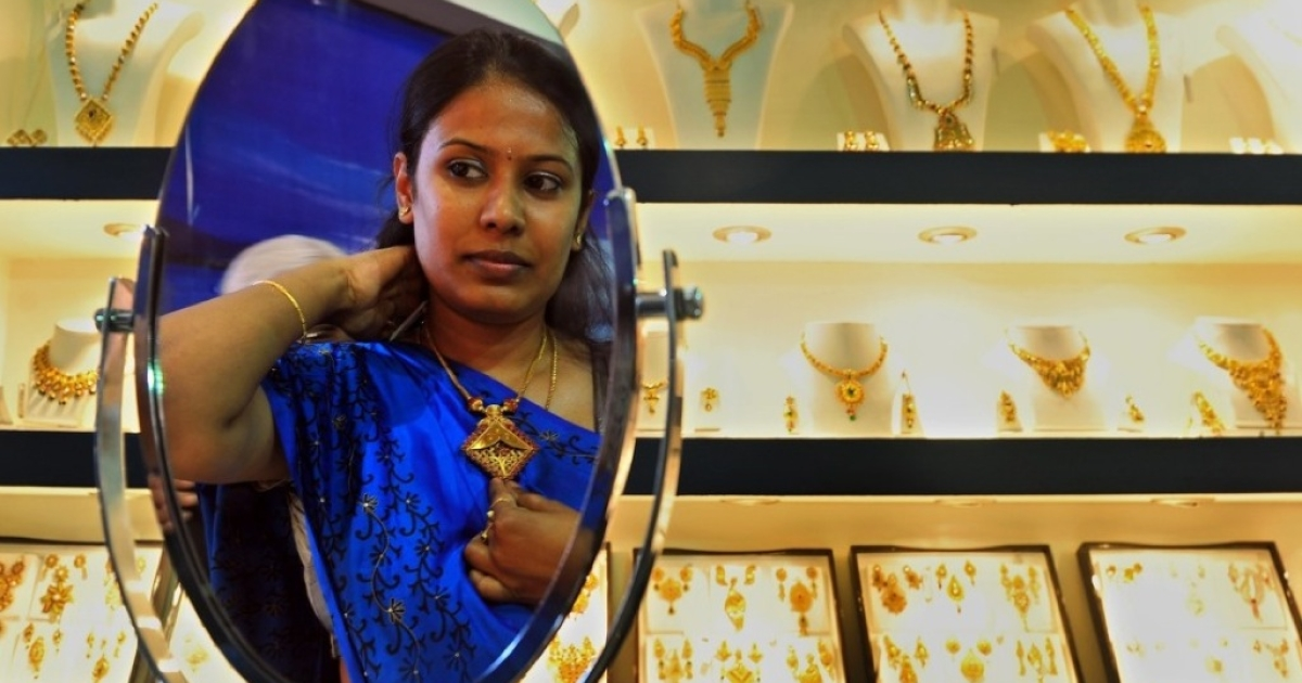 An Indian customer tries on a piece of gold jewelry.</p>