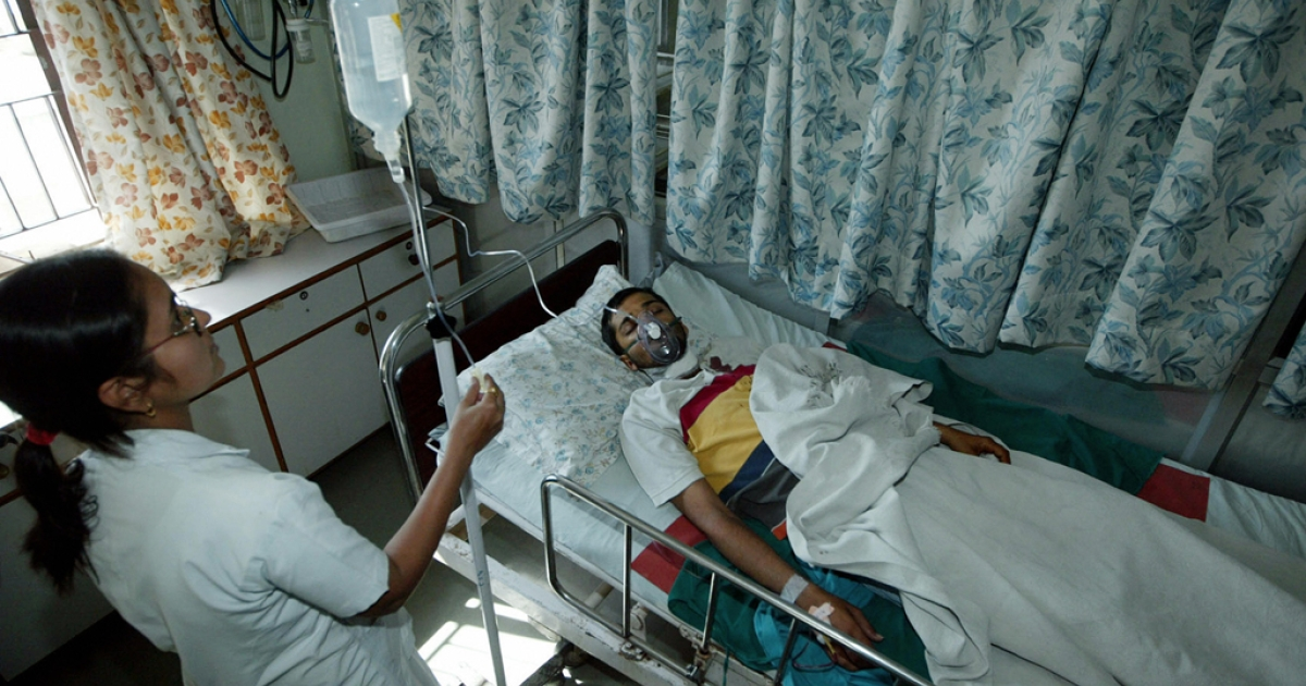 Indian photographer Bhadresh Gajjar, 31, lies on a hospital bed following treatment at a hospital in Ahmedabad, 14 January 2007.</p>