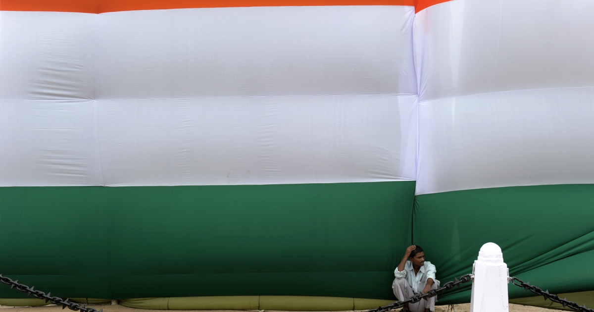 An Indian man sits in the shade of a huge Indian flag adorning the India Gate monument in New Delhi during Independence day celebrations on August 15, 2012. Indian Premier Manmohan Singh used his Independence Day speech to promise to improve conditions for foreign investment in the country after a sharp downturn in economic growth.</p>