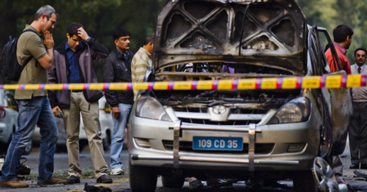 Unidentified foreigners survey the scene of a bomb blast as Indian Police and forensic officers examine a damaged Israeli embassy vehicle, on February 13, 2012 in New Delhi, India. A minor bomb blast struck an Israeli diplomats vehicle today injuring two people.</p>
