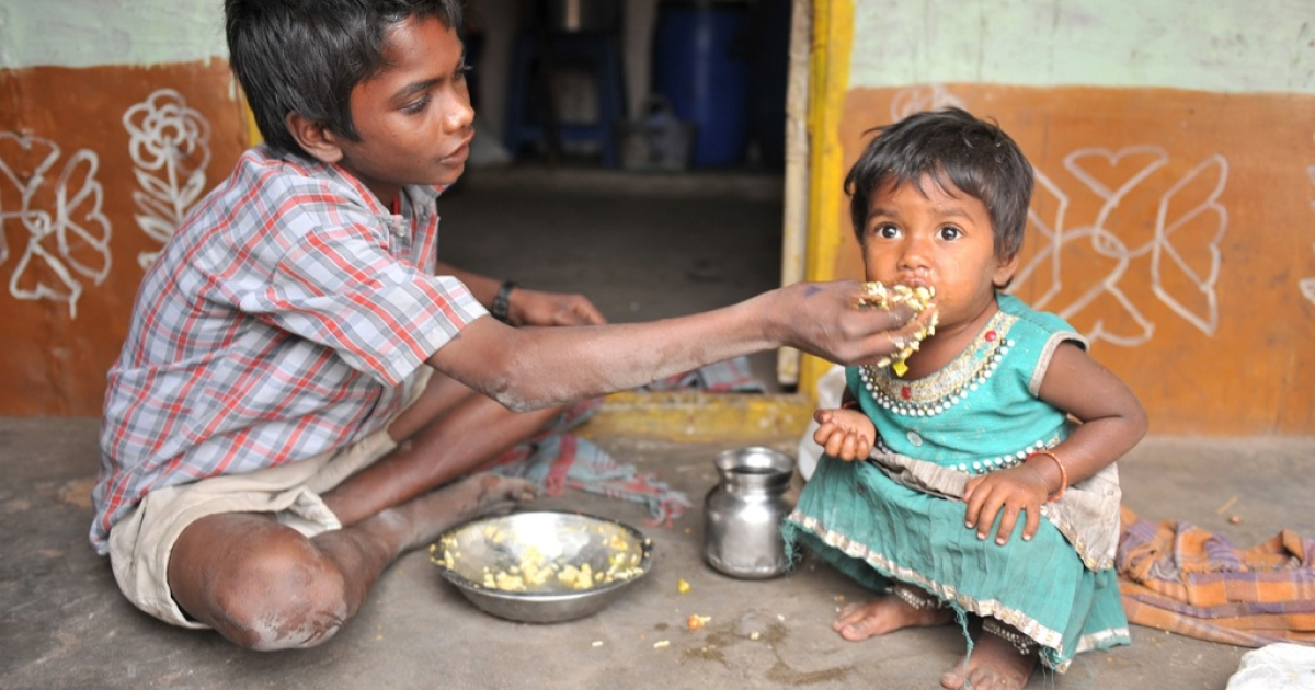An Indian boy feeds his sister at their home in a slum in Hyderabad, on January 10, 2012. Levels of under-nutrition in the country were 'unacceptably high' despite impressive GDP growth, Prime Minister Manmohan Singh said Tuesday and added that the problem of malnutrition was a 'national shame'.</p>