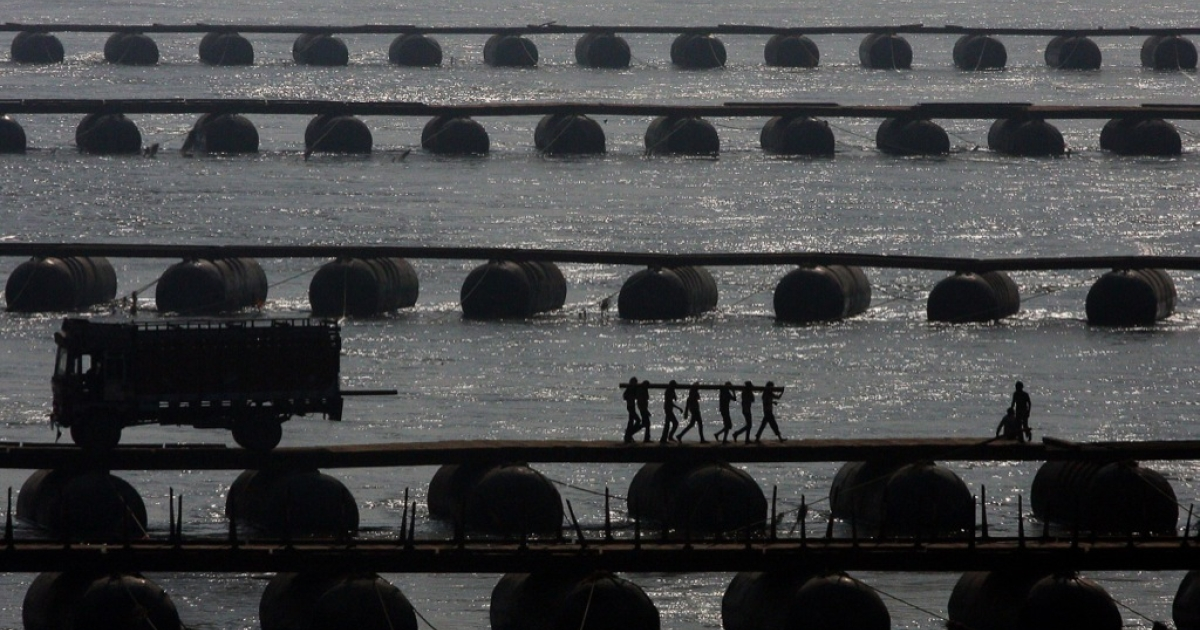 Indian labourers carry wood sleepers to construct a temporary pontoon bridge over the River Ganges at Allahabad on November 27, 2012.</p>