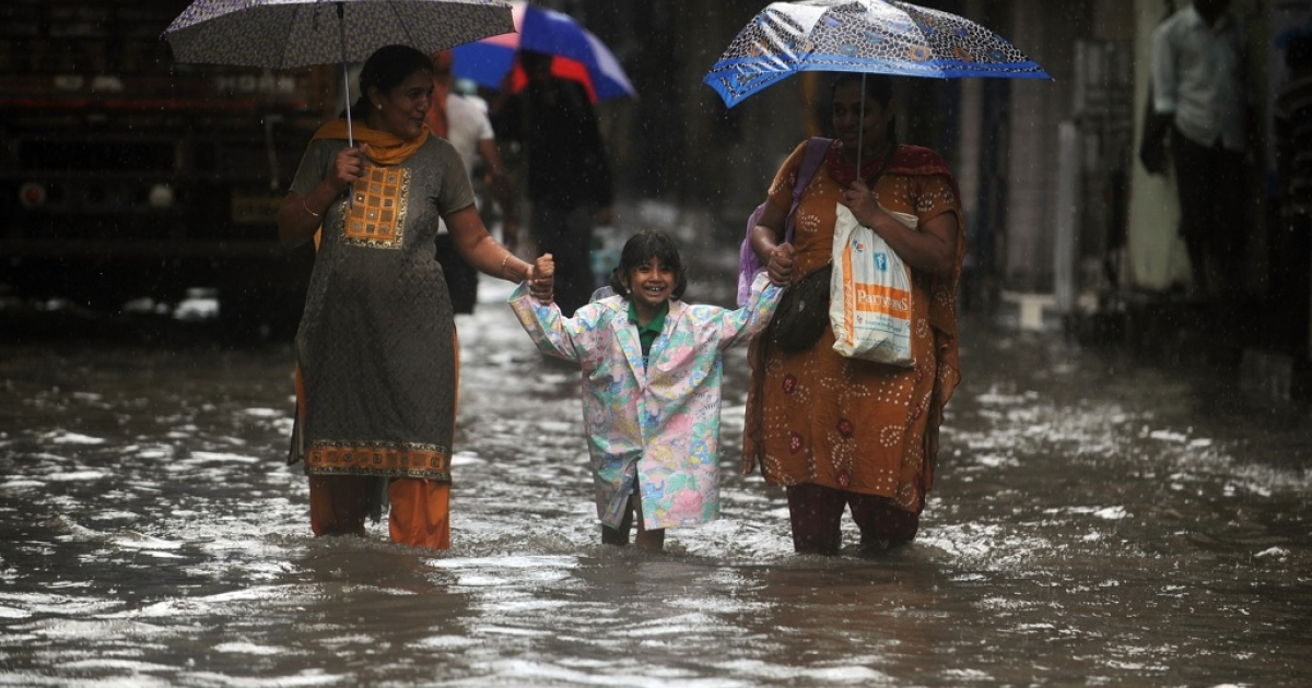 Indian pedestrians walk through a flooded street during heavy rains in Mumbai on August 27, 2012. The monsoon rains across the country has been more than 20 percent below its average, sparking fears of drought among farmers who remember vividly the failure of 2009, when India suffered its worst drought in nearly four decades.</p>