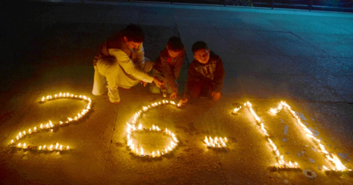 Three Indians light candels in tribute to victims, on the third anniversary of the 2008 Mumbai militant attacks, in Jammu on November 26, 2011. India reminded Pakistan November 26 it was still awaiting