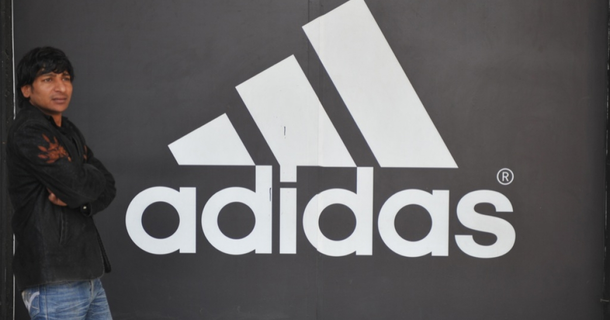 An Indian man stands next to the Adidas logo near the Adidas store in New Delhi on January 11, 2012.</p>