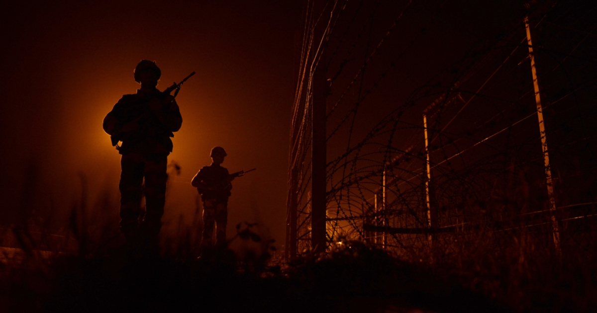 An Indian Border Security Force (BSF) soldiers patrols along the border fence at an outpost along the India-Pakistan border in Suchit-Garh, 36 kms southwest of Jammu on January 11, 2013.</p>