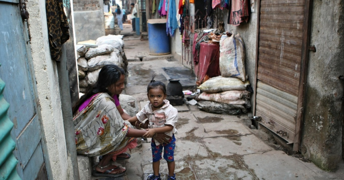 A mother tends to her child in Dharavi slum in Mumbai on January 20, 2009.</p>