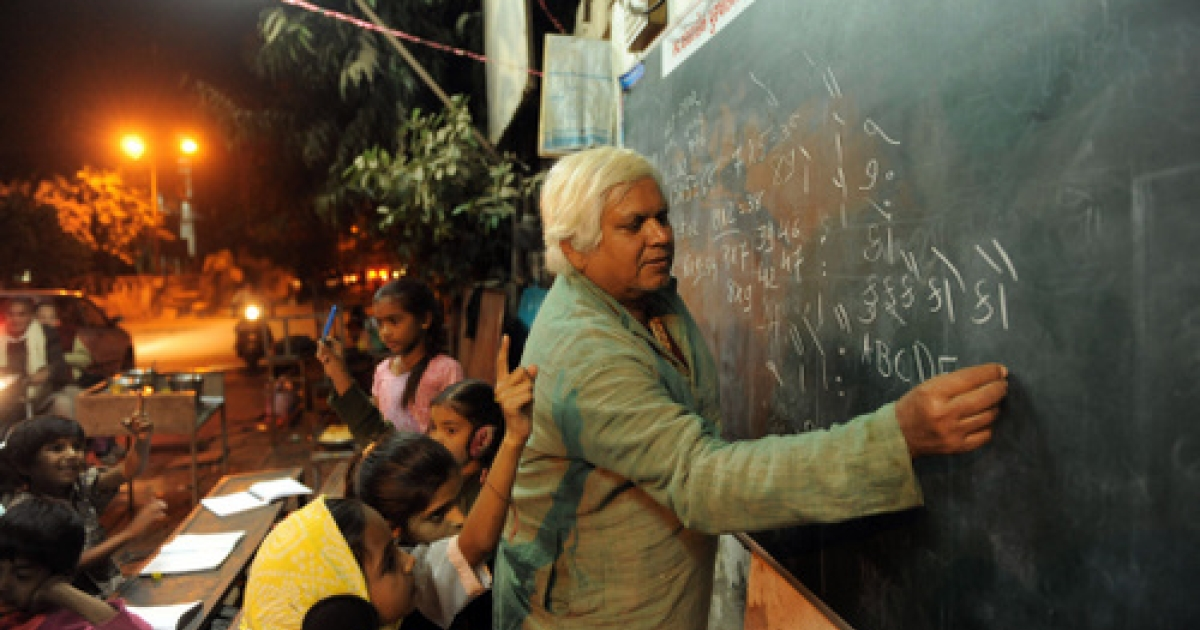Indian teacher Kamalbhai Parmar writes on a blackboard as Indian school students attend classes at a 'Footpath School' in Ahmedabad late on February 13, 2012. 'Footpath School' is the brainchild of Kamalbhai Parmar (65), who runs a business of metal fabrication and has been teaching his students on a footpath in Ahmedabad for the past twelve years. Parmar and his sons manage 'Footpath School'  for children of labourers, ragpickers and domestic servants where schoolchildren can receive extra tuition and a meal free of cost.</p>
