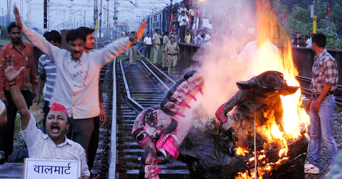 Samajwadi Party workers burning an effigy of Indian Prime Minister Manmohan Singh on the tracks as they stop a train in Allahabad on September 20, 2012. Opposition parties and trade unions called for shopkeepers, traders and laborers in India to block railway lines and close markets to protest against reforms.</p>