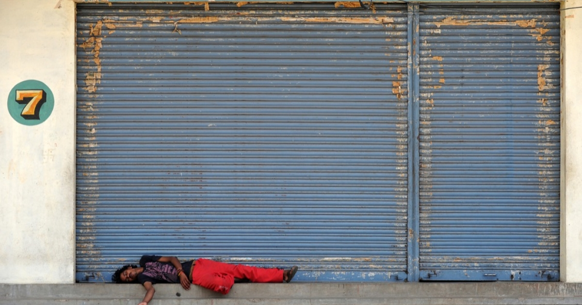 An Indian labourer sleeps in front of closed shops during a nationwide strike in Bangalore on September 20, 2012. Opposition parties and trade unions called for shopkeepers, traders and labourers in India to block railway lines and close markets to protest against reforms, designed by Prime Minister Manmohan Singh, to revive India's slowing economy allowing in foreign retail giants such as Walmart and Tesco.</p>