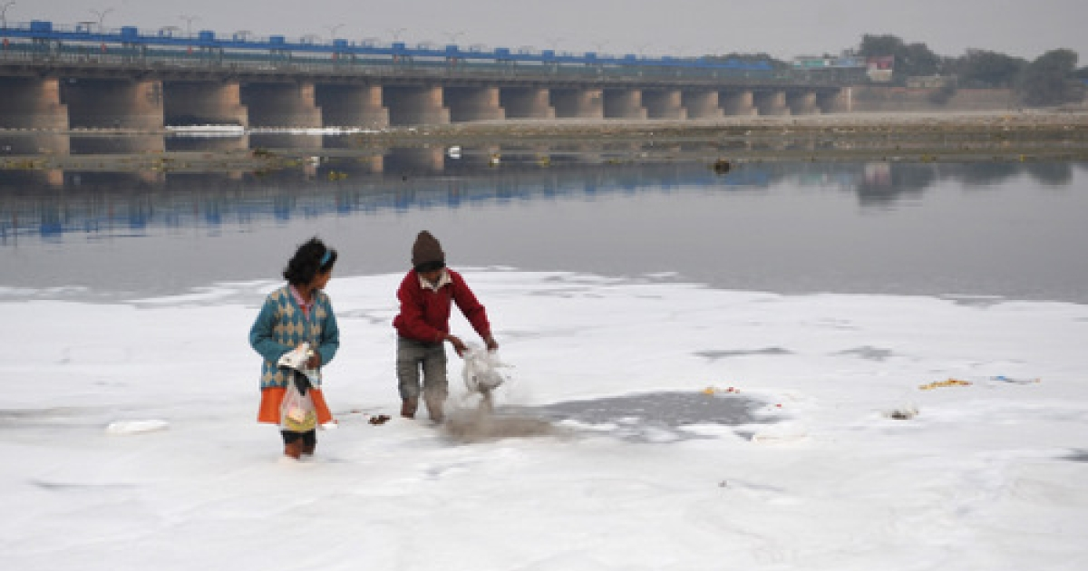 Indian children search for coins thrown in the polluted Yamuna river by Hindu devotees for ritual offerings in New Delhi on January 22, 2012. River Yamuna is one of the most polluted rivers of the country despite of the numerous efforts made to keep it clean. The main reason for pollution is the high density of the population living in the city and the dumping of untreated water and waste into the river. As per the figures, Delhi alone contributes around 3,296 MLD (million liters per day) of sewage in the river.</p>