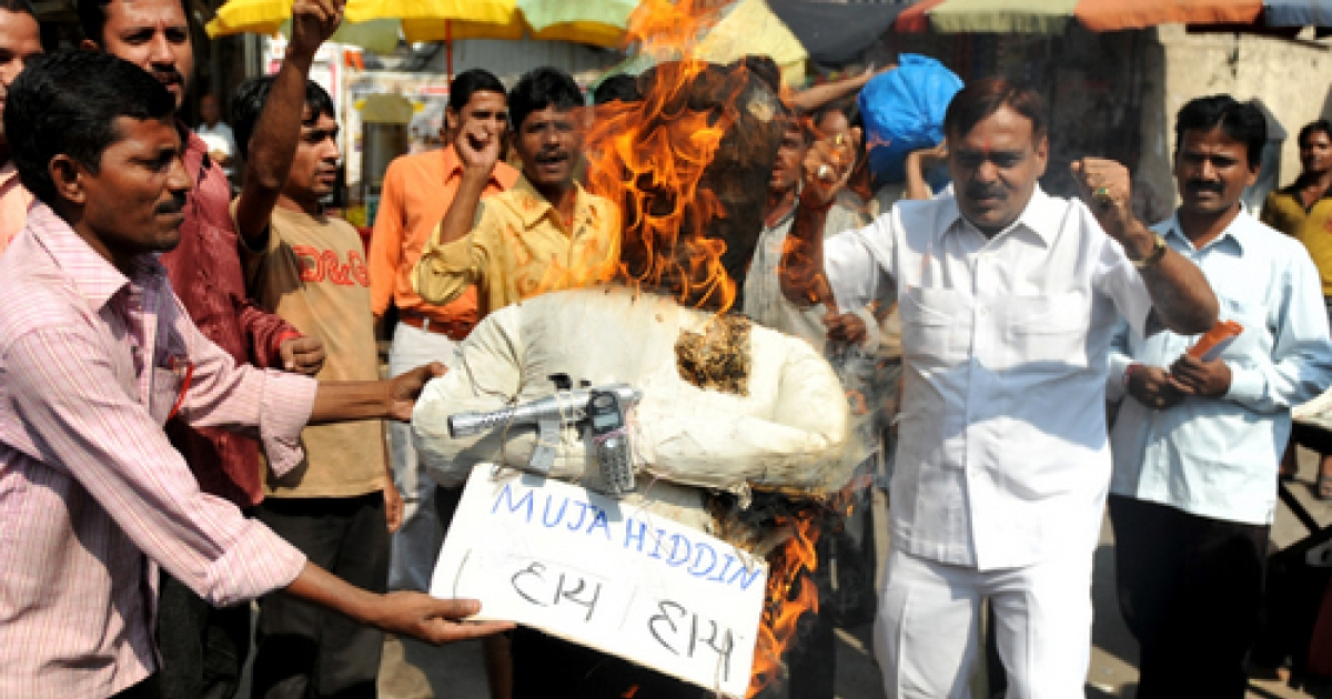 Activists from India's Congress Party shout slogans as they burn an effigy representing the 'Indian Mujahideen' organisation during a protest in Mumbai on Decemeber 8, 2010.</p>