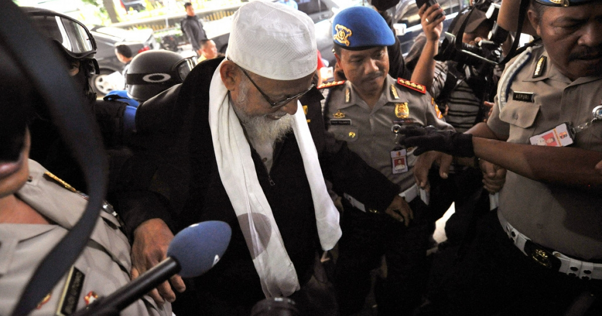 Elite anti-terror police escort arrested radical Islamist preacher Abu Bakar Bashir (C) on arrival at police headquarters in Jakarta on August 9, 2010. Bashir is accused of providing support for extremists linked with the Southeast Asian terror group Jemaah Islamiyah, officials said.</p>