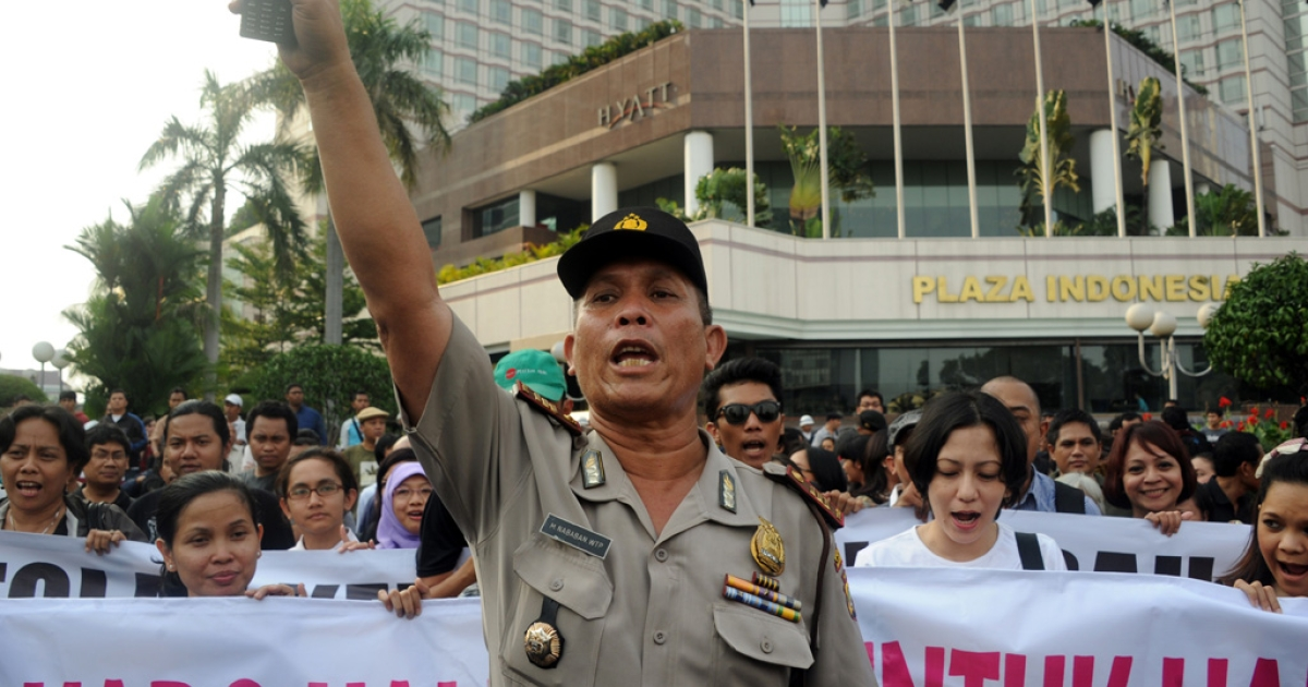 An Indonesian policeman gestures in front of protesters during a demonstration against the hardline Muslim group the Islamic Defender Front (flagged by the acronym FPI) in Jakarta on Feb. 14, 2012.</p>