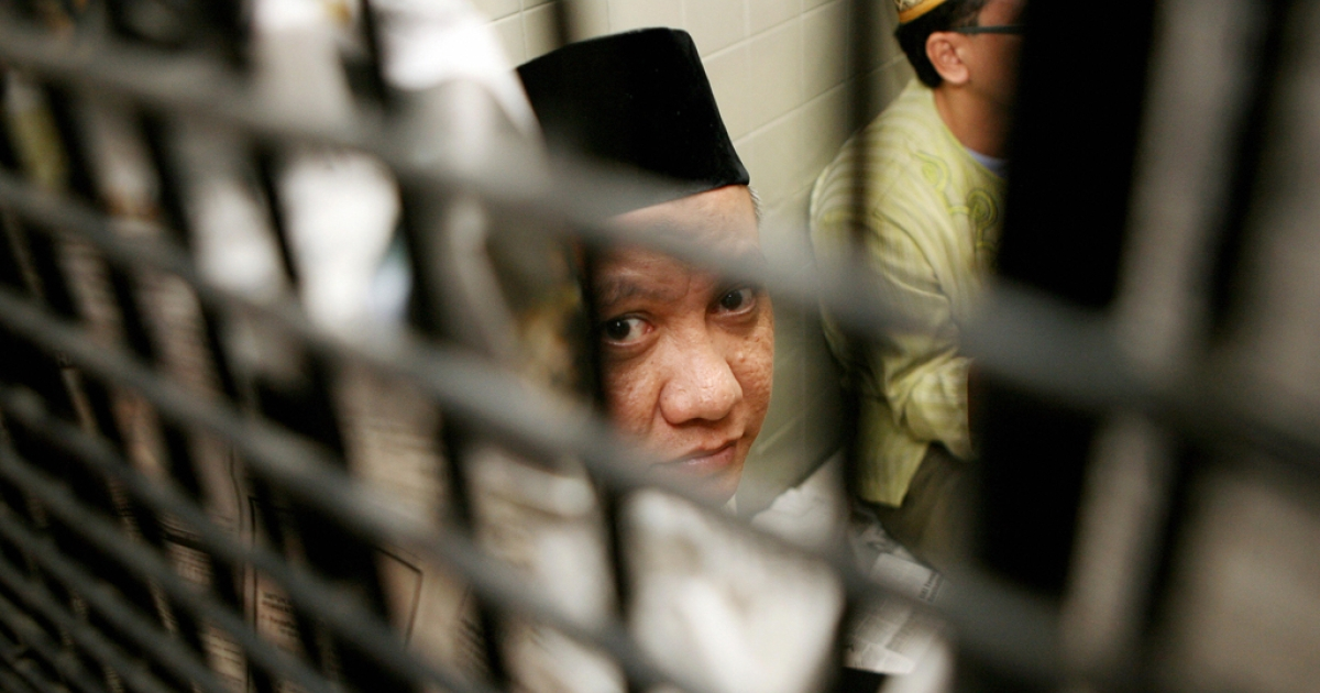 The leader of Islamic militant network Jemaah Islamiyah (JI) Zarkasi peers out of a cell at a court, before his first trial in Jakarta, Dec. 17, 2007.</p>