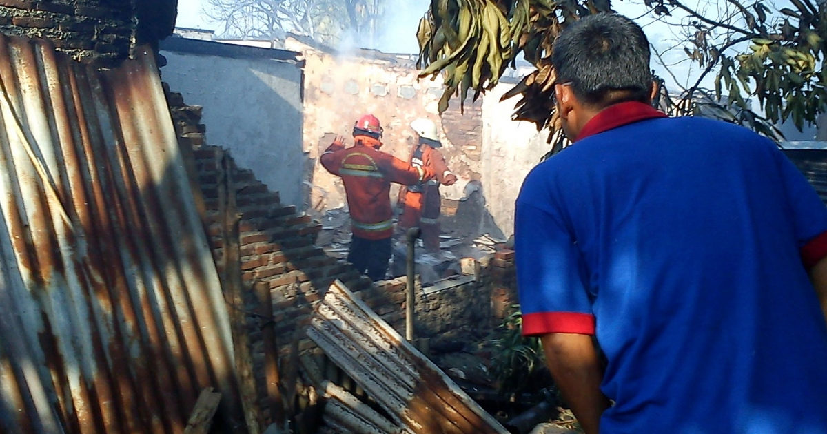 Emergency personnel (C) look through the rubble of a damaged building after an Indonesian military aircraft crashed in Jakarta on June 21, 2012.</p>