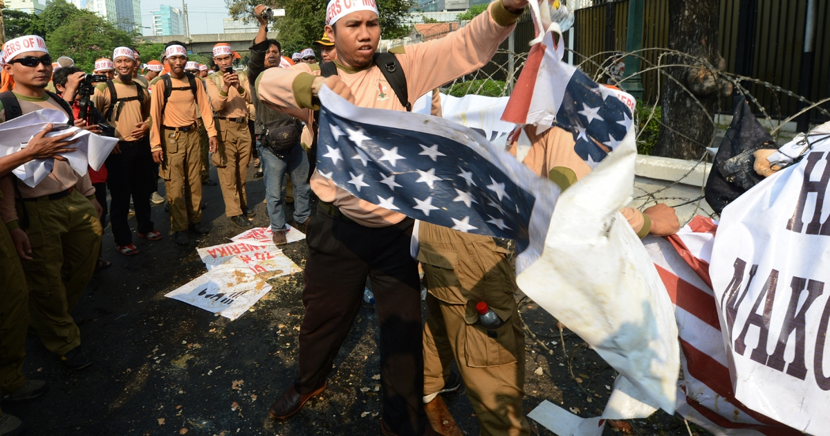 An Indonesian member of Justice and Prosperous Party (PKS) tears a copy of the US during a protest against a low-budget US film insulting to Muslims outside the US embassy in Jakarta on September 19, 2012.</p>