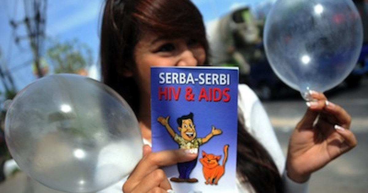 A woman displays inflated condoms during a World Aids Day campaign in Bali island on December 1, 2012.</p>