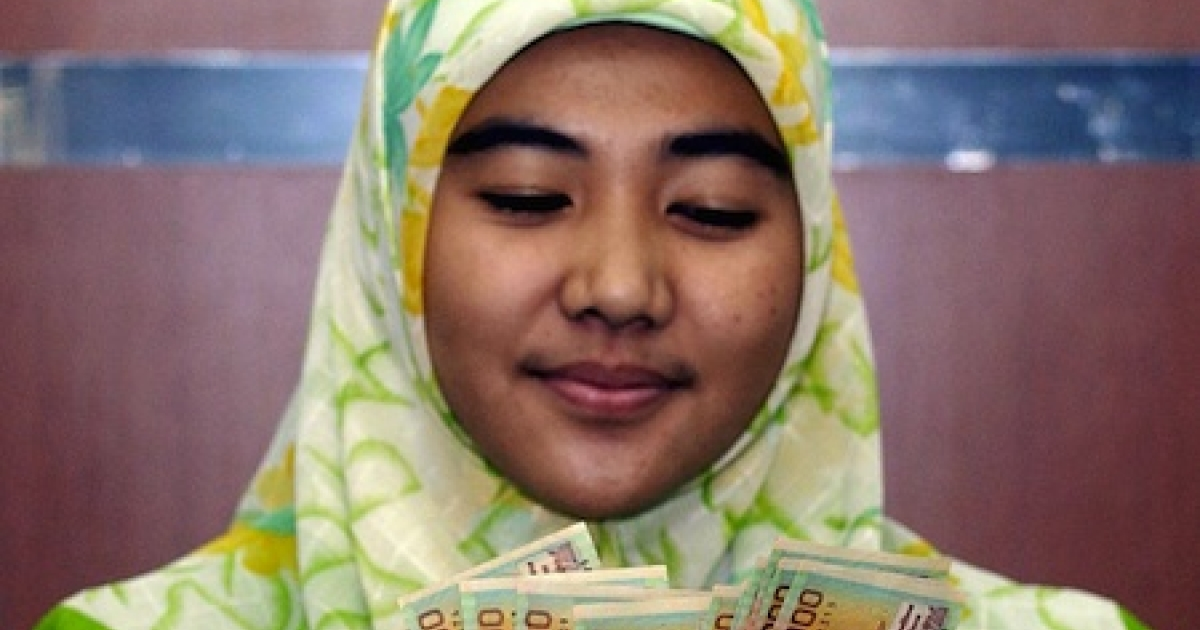 An employee of Bank Negara Indonesia's Islamic banking unit counts Indonesian rupiah from a customer in Jakarta in 2003.</p>