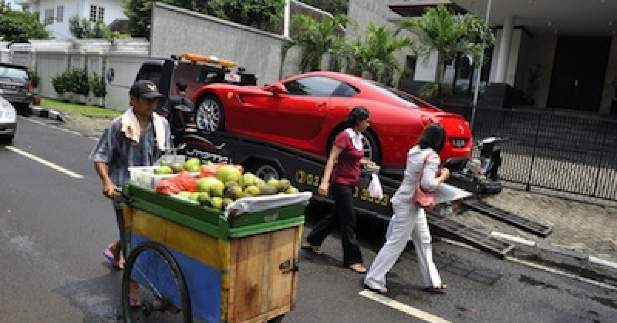 A street vendor pushes his cart past a luxury Ferrari sports car being delivered to the residence of a wealthy Indonesian resident at the affluent Menteng district in Jakarta on February 16, 2010.</p>
