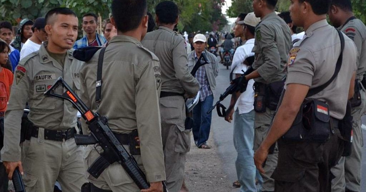 Indonesian policemen stand guard outside the compound of the Islamic boarding school following a blast that killed a man in Bima, West Nusa Tenggara on July 12, 2011.</p>