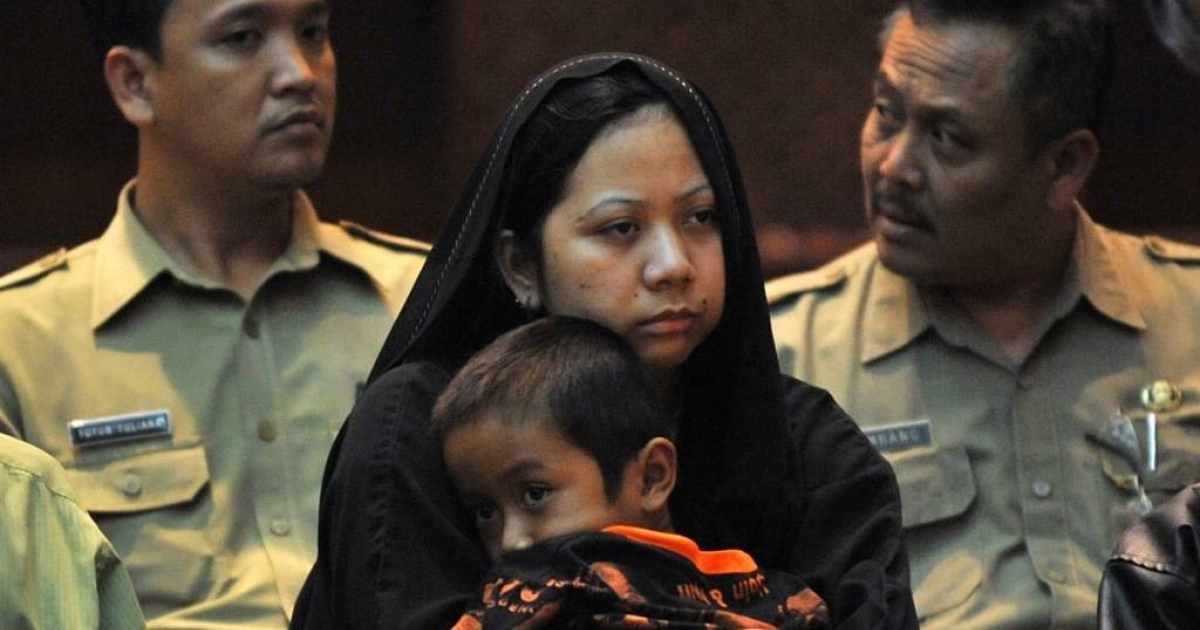 Darsem (C), an Indonesian maid who was convicted of murder in Saudi Arabia, holds her son during a handover ceremony in Jakarta on July 13, 2011.</p>