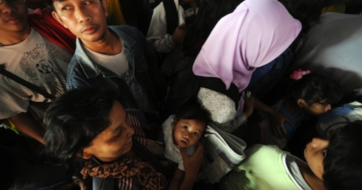 People queue to enter a train station in Jakarta on August 25, 2011. Millions of Indonesian Muslims are heading home to their villages to celebrate the Eid al-Fitr holidays with relatives.</p>