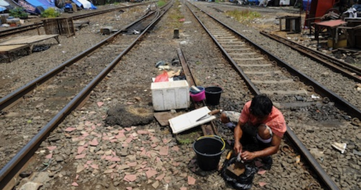 A vendor cleans fish amongst the railroad tracks in Jakarta on September 28, 2010. Some sick residents of West Jakarta have taken to lying across railroad tracks in hopes the electric current will somehow cure their ailments. The practice has spread to Malaysia.</p>