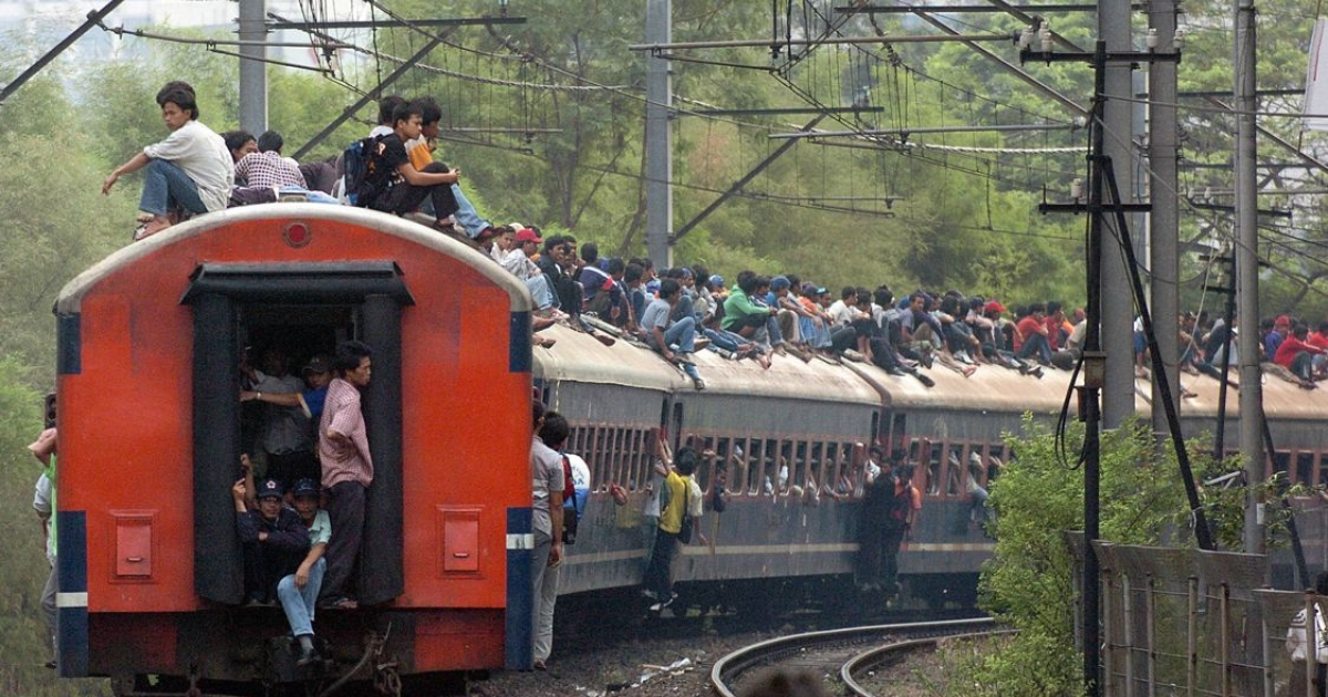 Commuters sit on top of a train as it pulls out of Palmerah station during rush hour in Jakarta, 29 June 2004.</p>