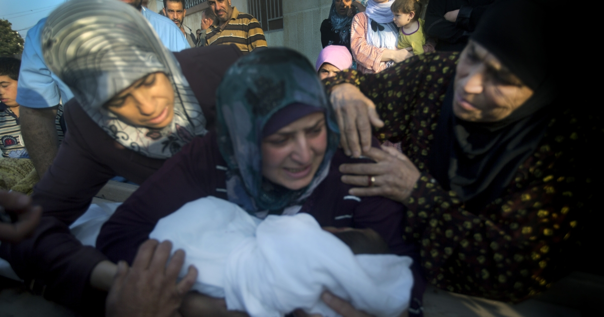 A mother holds the body of her 5 year-old son during his funeral after he was killed by a sniper outside the city of Homs.</p>