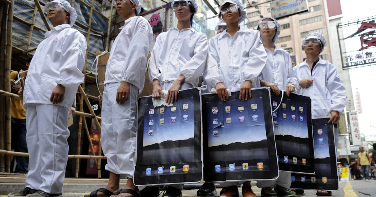 Participants dressed up to represent Foxconn workers take part in a protest against Taiwanese technology giant Foxconn, which manufactures Apple products in mainland China, outside an Apple retail outlet in Hong Kong. May 7, 2011.</p>