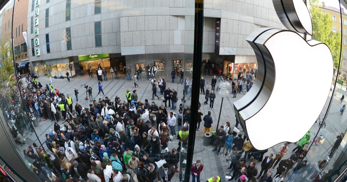 Customers queue to enter the Apple Store where a giant logo is displayed in the southern German city of Munich on September 21, 2012 as the iPhone 5 goes on sale.</p>