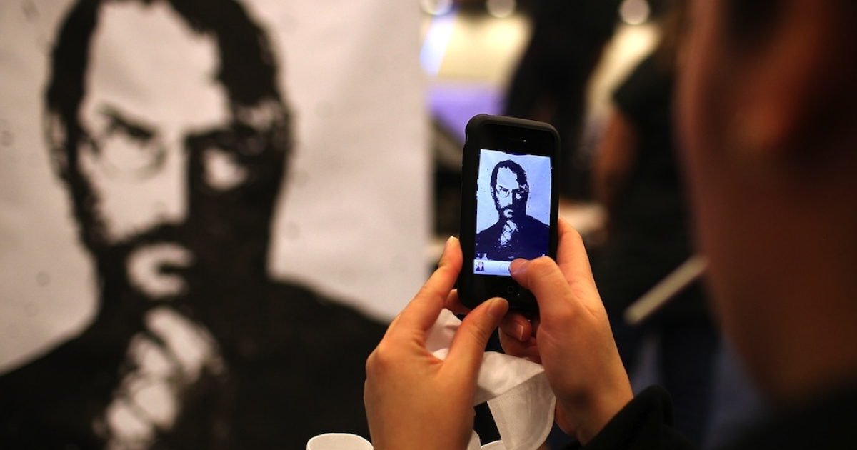 An iPhone user photographs a painting of former Apple CEO Steve Jobs during the Macworld iWorld Expo at the Moscone Convention Center on January 26, 2012 in San Francisco, California.</p>