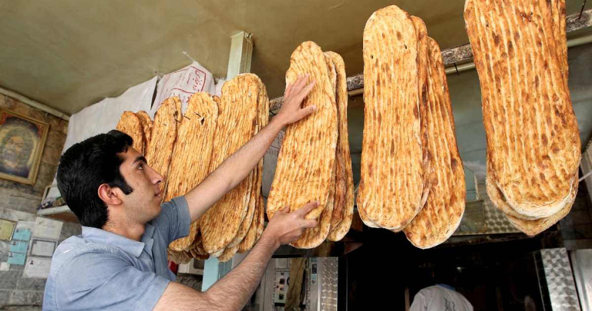 An Iranian baker displays loaves of bread at a bakery in central Tehran.</p>
