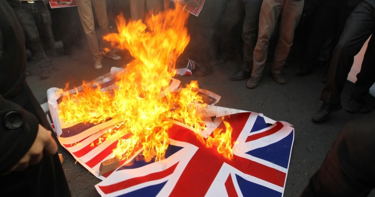 Iranian protesters burn the British flag outside the embassy in Tehran on Nov. 29, 2011.</p>