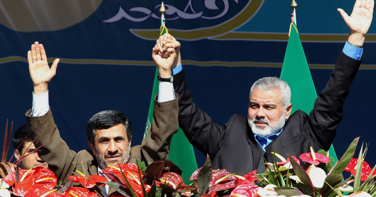 Iranian President Mahmoud Ahmadinejad (left) and Palestinian Hamas premier of Gaza, Ismail Haniya (right) wave to the crowd during the 33rd anniversary of the Islamic revolution in Azadi (Freedom) Square in southwestern Tehran on Feb. 11, 2012.</p>