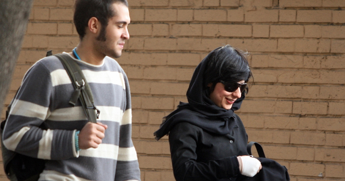 An Iranian man wearing western styled clothing walks with a woman wearing a loose headscarf in a street in Tehran, 12 November 2007.</p>