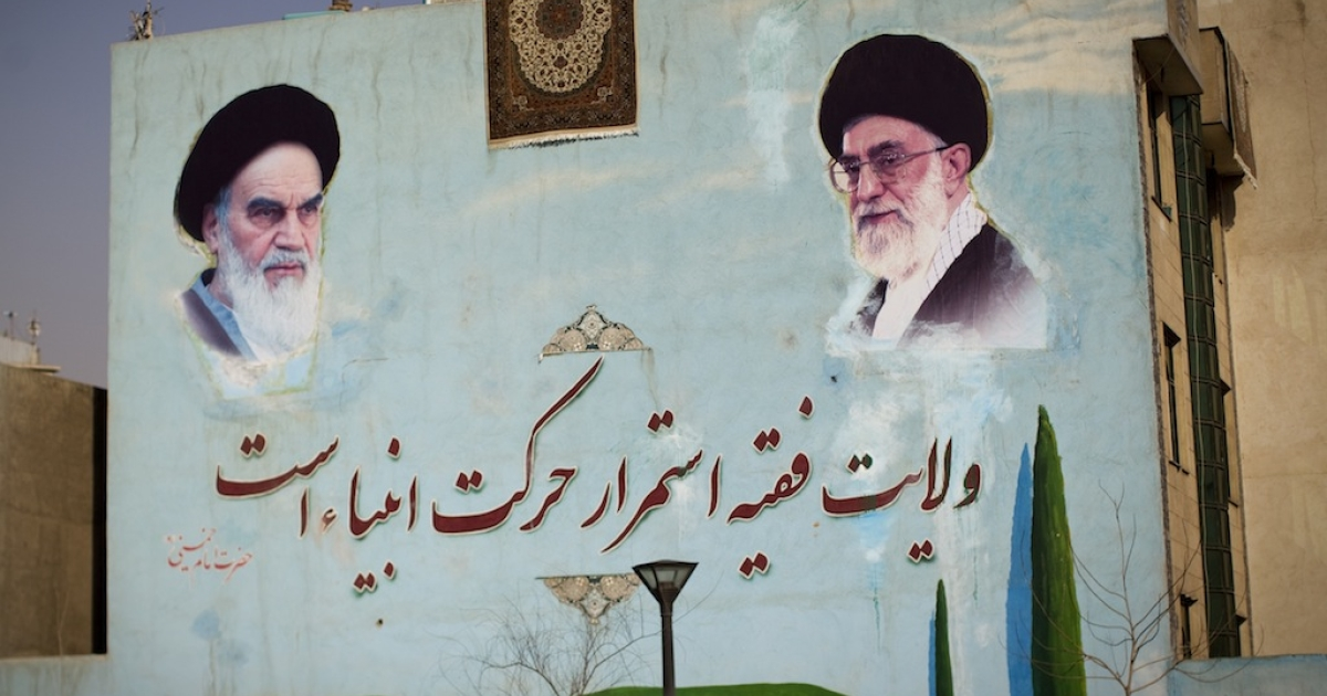 A washed carpet hangs from the roof of a building painted with a mural of the late founder of Islamic republic, Ayatollah Ruhollah Khomeini (L) and supreme leader, Ayatollah Ali Khamenei (R) are seen south of Tehran on Feb. 28, 2012.</p>