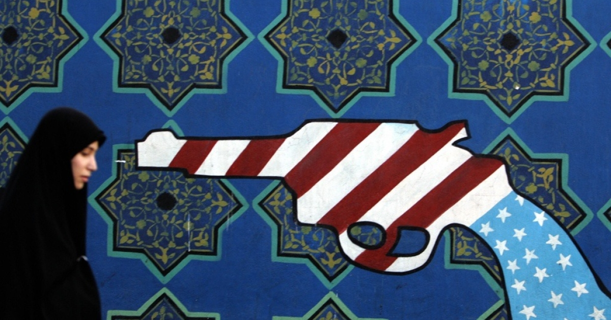 An Iranian woman walks past a mural painting of a revolver on the walls of the former US embassy in Tehran.</p>
