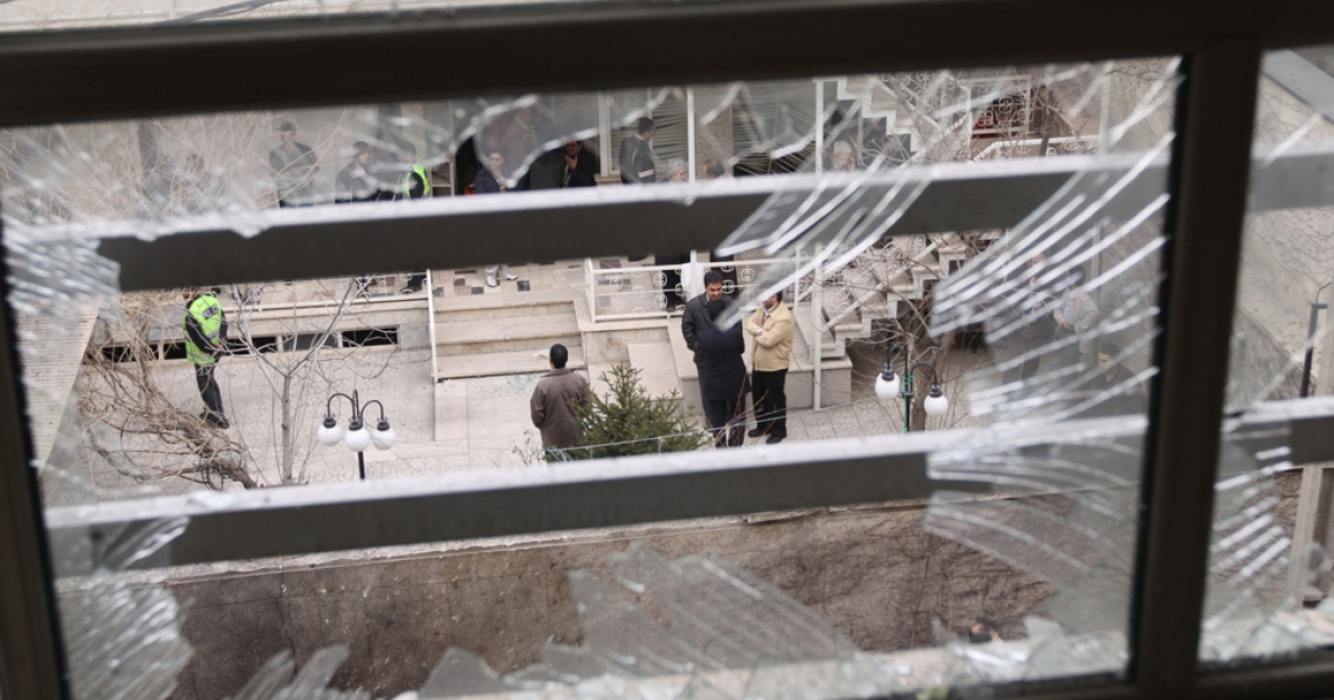 Iranian security agents are seen through a shattered window at the scene of a remote-controlled bomb explosion in which an Iranian university lecturer was killed outside his Tehran residence on January 12, 2010.</p>