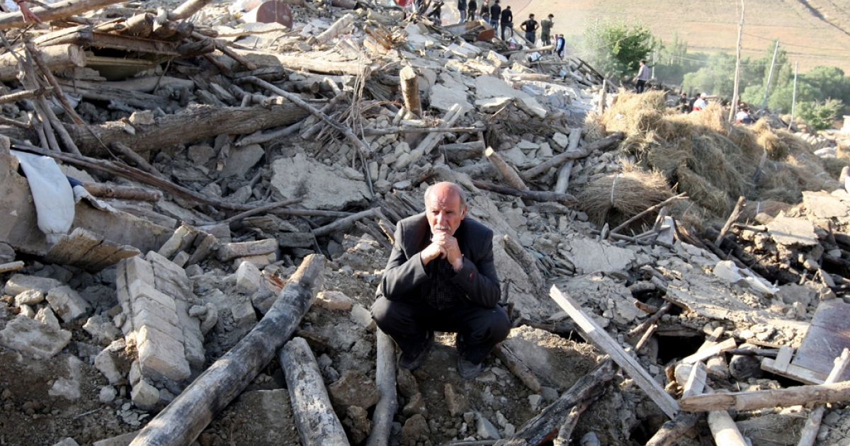 An Iranian resident from the village of Baje-Baj, near the town of Varzaqan,  stands on top of the rubble of his destroyed home on August 12, 2012, as rescue workers search for survivors, after twin earthquakes hit northwestern Iran on August 11.</p>