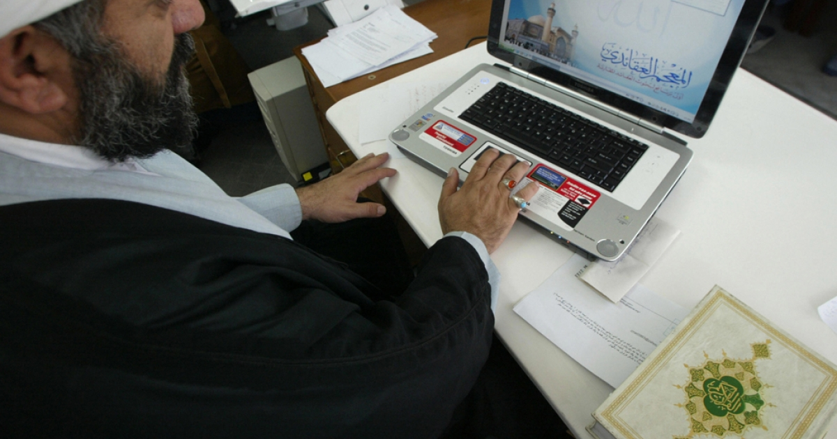 Iranian clergyman Nematollah Daneshmand works on his laptop with a copy of the Koran next to him at his office in Qom. The country has disrupted internet access ahead of national elections next week.</p>