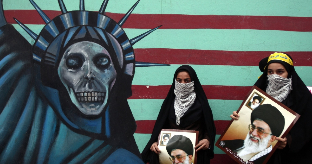 Iranian women hold pictures of Supreme Leader Ayatollah Khamenei outside the former U.S. embassy in Tehran on November 4, 2011, during a rally to mark the storming of the American embassy by Iranian students 32 years ago.</p>